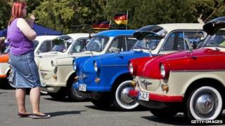 A woman looks at a row of Trabants at a car festival