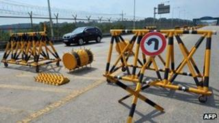 A car drives past barricades on the road linking North Korea's Kaesong Industrial Complex at a military check point in Paju near the demilitarized zone dividing the two Koreas on 6 June 2013