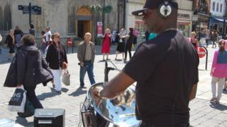 Jamma, from Birmingham, busking with a steel pan in Gloucester