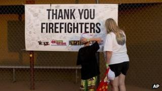 Lyam Davis, left, watches as his mother, Rachel Davis, sign a banner during the Fourth of July celebration in Prescott, Arizona , 4 July 2013