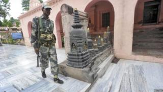 An Indian security personnel walks next to bloody footprints inside the Mahabodhi temple complex, after a series of explosions at Bodh Gaya in the eastern Indian state of Bihar July 7, 2013