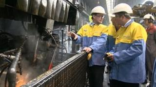 Minister Greg Barker (left) being shown around the Corby steelworks