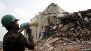 Man in front of collapsed building