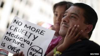 Ever, 40, holds his daughter Darlyne, 5, at a rally in Los Angeles, California 1 August 2011