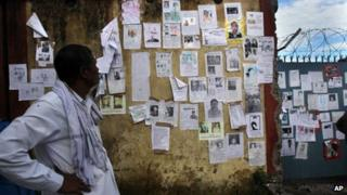 A man looks at a wall covered with pictures of missing people near the airport in northern Indian state of Uttarakhand on June 26, 2013