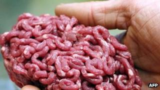 A man holds minced beef meat