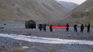 """In this May 5, 2013 photo, Chinese troops hold a banner which reads: """"You've crossed the border, please go back,"""" in Ladakh, India"""