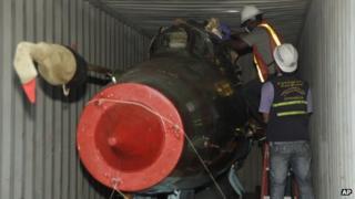 Men inspect military material found aboard the North Korean ship Chong Chon Gang