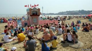 Crowds gather to watch a Punch and Judy show in Weymouth