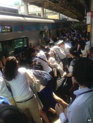 Train passengers and railway staff push a train car to rescue a woman stuck between the car and the platform at Japan Railway Minami Urawa Station in Saitama, near Tokyo, on 22 July 2013