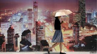 Beijing resident walks past wall bearing image of skyscrapers (23 July)