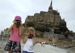 Two girls take photos at Mont-Saint-Michel