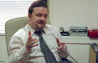 Ricky Gervais as David Brent in The Office, sat behind his desk pointing at the camera with both hands