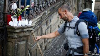 A pilgrim leaves his cane next to candles in memory of the train crash victims at the Cathedral of Santiago