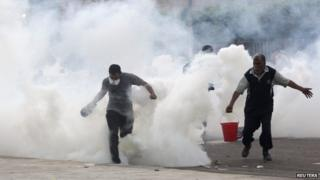 Supporters of former president Mohammed Morsi run from tear gas fired by police