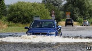 Car drives through flood water in Loughborough on 28 July 2013