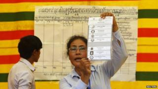 An election official displays a ballot paper