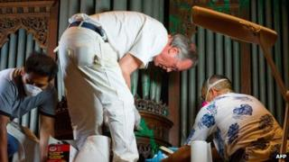 A crew removes green paint from an organ at the Washington National Cathedral, in Washington DC on 30 July 2013