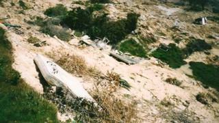 A mattress and some of the remains of Boma Cottage down the side of the cliffs