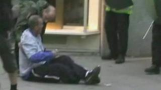 Ian Tomlinson sitting on the pavement after being pushed over