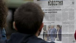 """street cafe visitor reads a fresh Russian newspaper """"Izvestia"""" with a front page pictures of Russian lawyer Anatoly Kucherena, centre, and National Security Agency leaker Edward Snowden, centre left"""