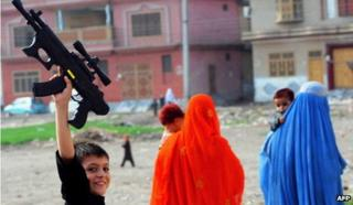A Pakistani boy, fleeing from military operations against Taliban in the Pakistani tribal region, plays with toy guns