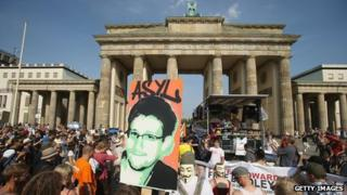 """A participant holds up a picture of former Edward Snowden with the word """"asylum"""" written above it at a protest gathering in front of the Brandenburg Gate on July 27, 2013 in Berlin, Germany"""