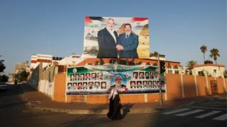 Palestinian girls walk in front of billboard showing former Egyptian President Mohammed Morsi shaking hands with Hamas Prime Minister Ismail Haniyeh on 29 August 2012