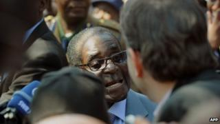 Robert Mugabe (C) answers journalists questions after voting at a polling station at a school in Harare on 31 July