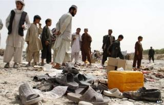 Afghan men walk amidst sandals, mostly from victims of a bomb blast, strewn at the roadside on the outskirts of Kandahar on August 5, 2013.