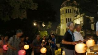 Buddhist followers hold paper lanterns as they march in prayer for peace, around the illuminated Atomic Bomb Dome in Hiroshima, western Japan Monday, 5 Aug. 2013