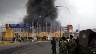 Policemen stand guard as fire rages at the International arrivals unit of Jomo Kenyatta International Airport, Nairobi, Kenya