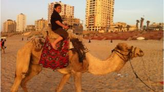 Child rides a camel on the beach in the Gaza strip