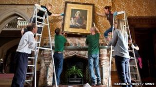The painting being re-hung
