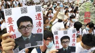 "In this image taken on 20 July 2013, in Taipei, Taiwan, protesters hold posters that read ""Give the truth"" next to portraits of Taiwan soldier Hung Chung-chiu, who died in early July after being forced to perform a vigorous regime of calisthenics in sweltering heat on a base in suburban Taipei"