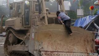 A supporter of deposed Egyptian President Mohamed Morsi jumps on a bulldozer clearing their sit-in site of the past six weeks at Rabaa Adawiya square in Cairo, 14 August, 2013.
