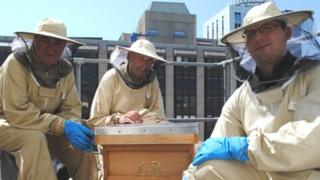Steve Harris (l) and Scott Frankton (r) from the Royal Hotel pictured with bee keeper Peter Shaw by the Royal Hotel hive