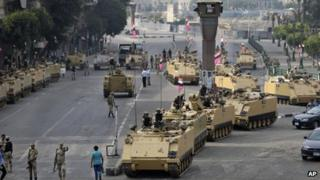 Egyptian army soldiers take their positions on top and next to their armoured vehicles while guarding an entrance to Tahrir Square, Cairo