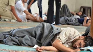 A man, who Syrian opposition activists say survived a chemical weapon attack, rests in a mosque in Douma, Damascus (21 August 2013)