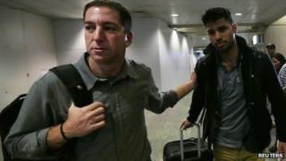 Glenn Greenwald (left) and his partner David Miranda (right) were reunited when Mr Miranda arrived back in Brazil