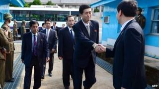 A South Korean official (R) greets a North Korean negotiation team for Red Cross talks as the team crosses the border line at the truce village of Panmunjom in the Demilitarized Zone dividing the two Koreas on 23 August 2013
