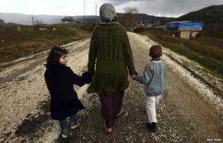 A female refugee holds her children's hands