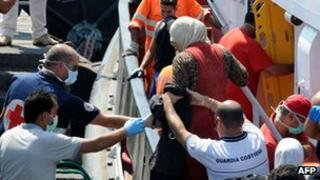 Migrants being helped ashore in Sicily, 19 Aug 13