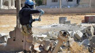 A member of a UN investigation team takes samples of sands near a part of a missile in the Damascus countryside of Ain Terma, Syria, on Wednesday, in an image provided by the United media office of Arbeen