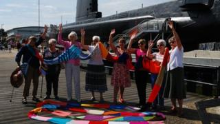 Local knitting group Priddys Purlers revealing part of the giant scarf in front of HMS Alliance