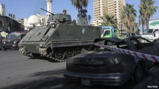 A Lebanese army armoured personnel carrier patrols the street in front of al-Takwa mosque where a second car bomb exploded in the port city of Tripoli in northern Lebanon 24 August, 2013