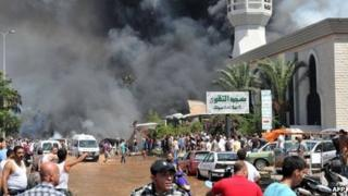 Smoke is seen above people gathering outside a mosque on the site of a powerful explosion in the northern Lebanese city of Tripoli on 23 August, 2013.