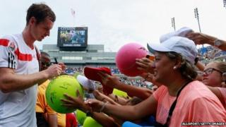 Andy Murray signs a giant tennis ball for a fan
