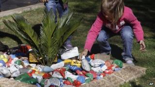 A child place painted pebbles with get-well messages in a garden for former president Nelson Mandela, outside his Johannesburg home Saturday, Aug. 31, 2013.