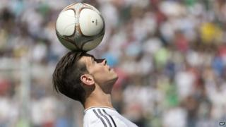 Gareth Bale balances a ball on his head